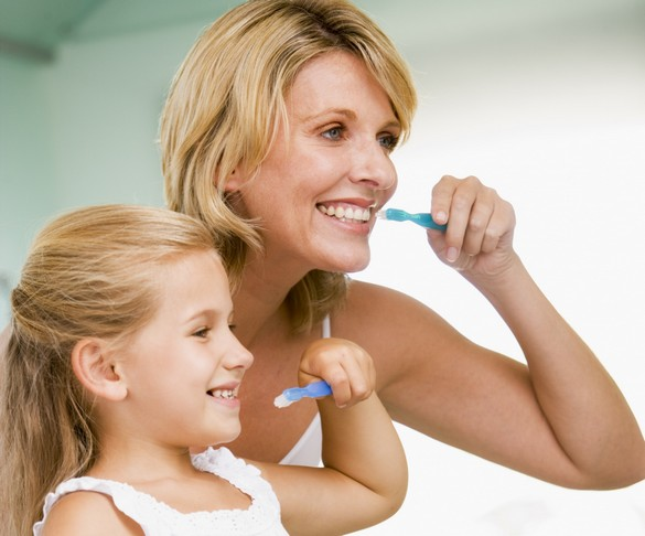 Pour montrer à votre enfant la bonne façon de se brosser les dents, le mieux est de vous placer derrière lui, face à la glace. ©Phovoir